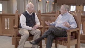 Doug Kelly and Del Tackett talking in a church