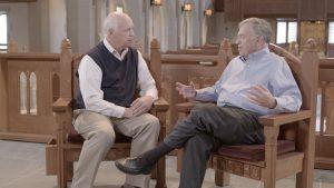 Doug Kelly and Del Tackett talking in a church